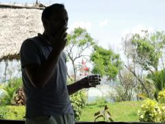 Young man smoking cigarette on country house porch NTSC Stock Footage