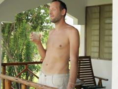 Happy shirtless man drinking water on country house porch NTSC Stock Footage