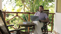 Man working on modern laptop on country house porch HD Stock Footage