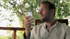 Man listening to music on smartphone on house porch HD Stock Footage