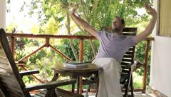 Young happy man relaxing on country house veranda HD Stock Footage