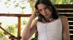 Pensive, thoughtful woman listening to sad song on smartphone HD Stock Footage