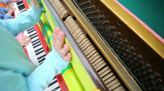Children hands playing at piano during the day Stock Footage