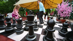 Boy teaching girl to play chess on big chessboard Stock Footage
