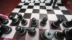 Children feet moving chess pieces on big chessboard Stock Footage