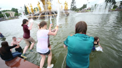 Several girls jumping in water in fountain during the day at VVC Stock Footage