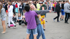 Young boy and girl hugging in crowd during the day at VVC Stock Footage