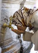 woman washing face in holy water mevlana konya turkey - stock photo