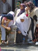 drinking holy water mevlana konya turkey - stock photo