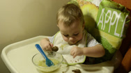 Stock Video Footage of Baby girl is eating porridge with bread from a glass plate