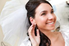 Happy bride touching her ear-ring Stock Photos