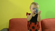 Stock Video Footage of Baby in ladybird costume drinks from bottle on the couch