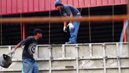 Worker toss up a bucket of concrete to other worker above Stock Footage