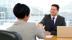 Handsome businessman shaking hands with interviewee - stock footage