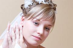 Beautiful bride thingfully puts on an ear-ring Stock Photos