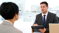 Handsome businessman talking with interviewee holding clipboard Stock Footage