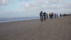 Mountain bikers in the beach race Egmond-Pier-Egmond ride along the sea shore Stock Footage