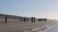 Mountain bikers in the beach race Egmond-Pier-Egmond ride along the sea shore Stock Footage