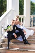 Bride and groom on the stairs of the summer house Stock Photos