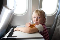 Child with juice in airplane Stock Photos