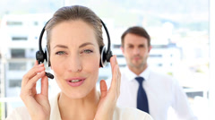 Call centre agent speaking with colleague behind her - stock footage