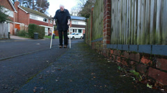 Elderly man using crutches after hip operation (Surburbia) Stock Footage