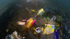 Plastic garbage and other trash underwater in tide mark Stock Footage
