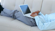 Stock Video Footage of Businessman falling asleep on the couch with laptop