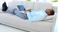 Stock Video Footage of Businessman falling asleep on the sofa with laptop