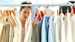 Fashion designer looking through her clothing rail Stock Footage