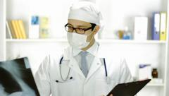 Portrait Doctor White Mask Looking Xray Writing Down Diagnosis - stock footage