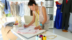 Fashion designer sketching a design at table - stock footage
