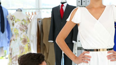Designer adjusting hemline of dress on model Stock Footage