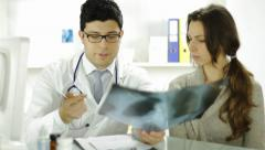 Doctor and Patient Looking at Xray Writing Prescription Stock Footage