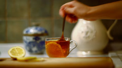 Mixing lemon and sugar in glass cup of tea, beautiful soft focus shot Stock Footage