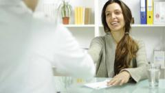 Young Female Talking to Doctor Medical Practitioner Smiling - stock footage