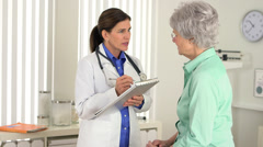 Senior doctor taking notes while talking to patient Stock Footage