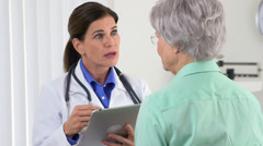 Senior doctor talking to patient with tablet Stock Footage