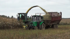 Maize field work harvester cut pour grain into tractor trailer Stock Footage