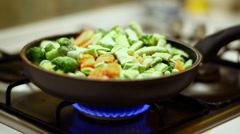 Frying and mixing frosted vegetables on natural blue gas Stock Footage