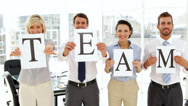 Stock Video Footage of Business people holding up pages spelling out team