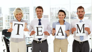 Stock Video Footage of Happy business people holding up pages spelling out team