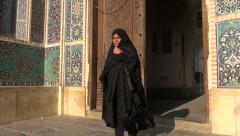 Iran, veiled lady in black chadors exits mosque Stock Footage