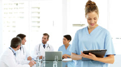 Nurse smiling at camera while staff are talking behind her - stock footage