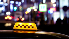 Timelapse of city traffic at night behind taxi sign Stock Footage