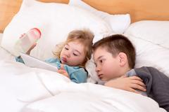 Cute little boy and girl reading before sleeping Stock Photos