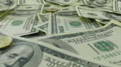 US currency gold coins falling on one hundred dollar bills Stock Footage