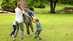 Happy family playing ring a rosie in the park together Stock Footage