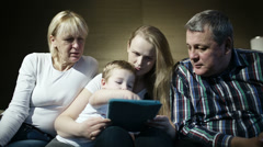 Family watching boy playing game on touchpad Stock Footage