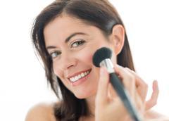 attractive woman in her forties applying makeup - stock photo